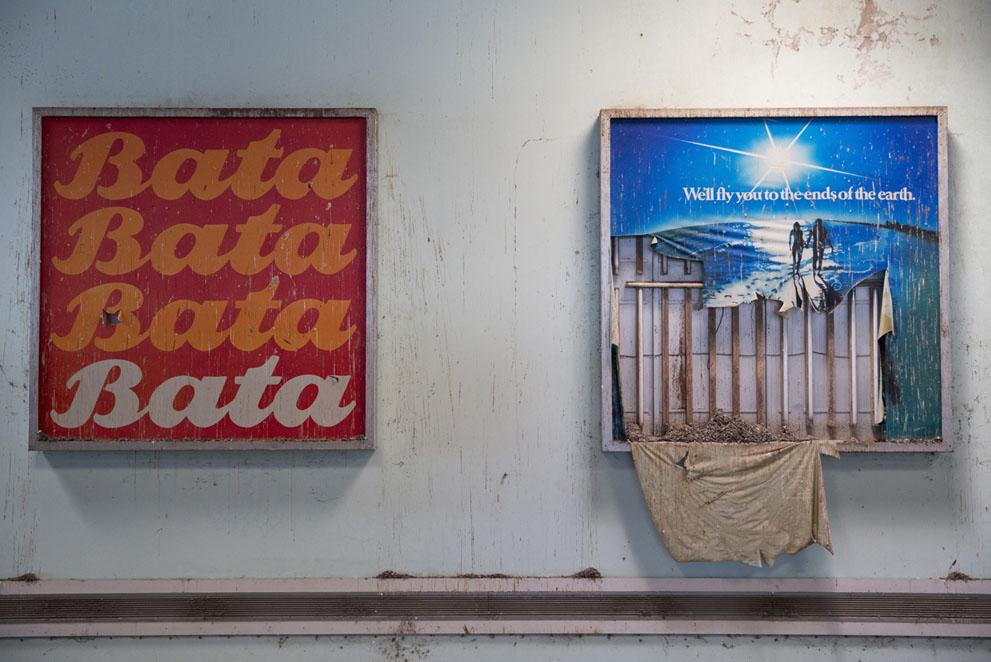 Обветшалые рекламные плакаты на стенах аэропорта