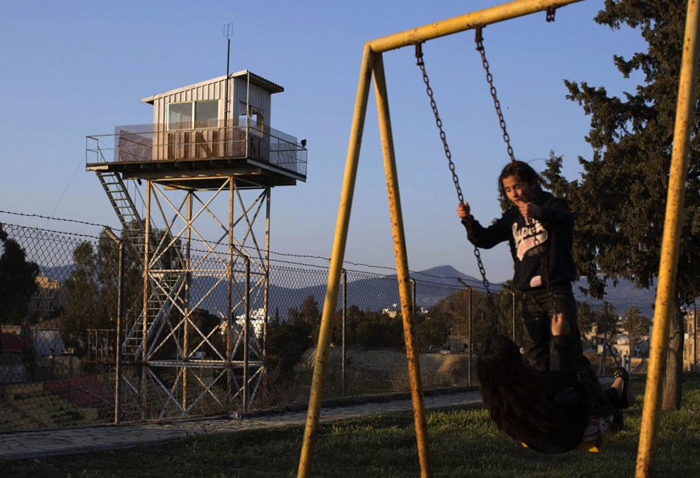 Дети в парке рядом с забором
