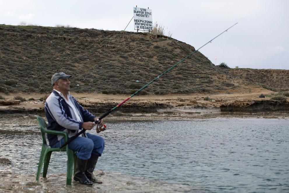 Рыбак на фоне знака на границе буферной зоны